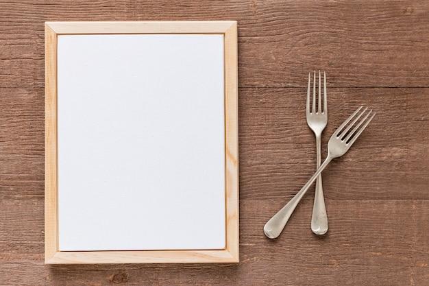 Disposizione piana della carta in bianco del menu con la coltelleria su superficie di legno