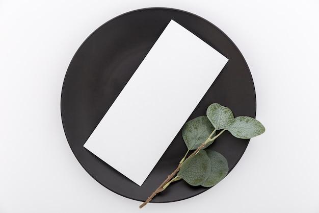 Disposizione piana della carta in bianco del menu sul piatto con la pianta