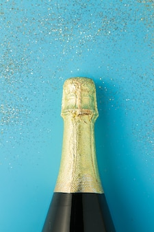 Disposizione piana della celebrazione, bottiglia di champagne su fondo blu con scintillio.