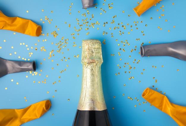 Disposizione piana della celebrazione, bottiglia e pallone di champagne su fondo blu con scintillio.