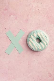 Disposizione piana della ciambella glassata con la lettera x