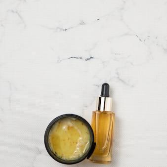 Disposizione piana della crema e della bottiglia di olio essenziale su fondo di marmo