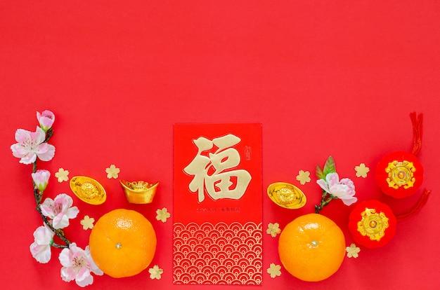 Disposizione piana della decorazione cinese di festival del nuovo anno su fondo rosso. la lingua cinese sul pacchetto rosso di lingotti e denaro significa benedizione