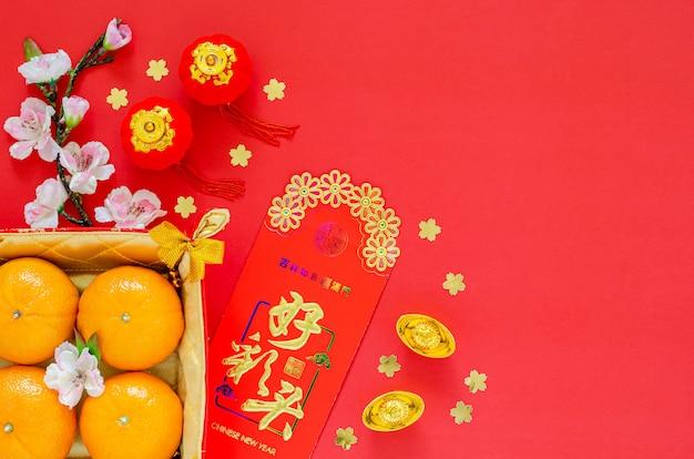 Disposizione piana della decorazione cinese di festival del nuovo anno su fondo rosso. lingua cinese sul lingotto significa benedizione, sul pacchetto rosso denaro significa