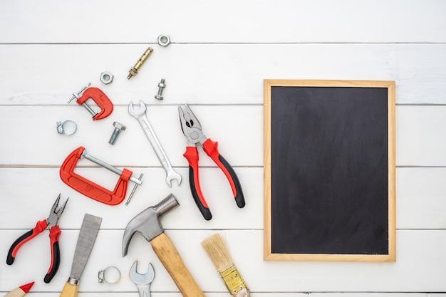 Disposizione piana della lavagna dello spazio in bianco con gli strumenti pratici della costruzione sopra fondo di legno.