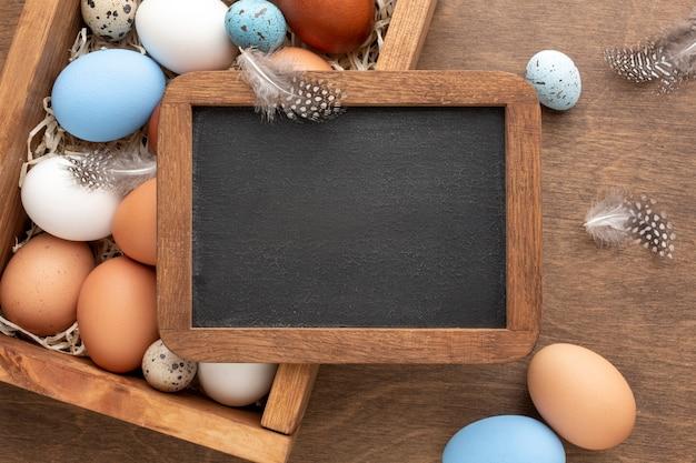 Disposizione piana della lavagna sopra la scatola con le uova per pasqua