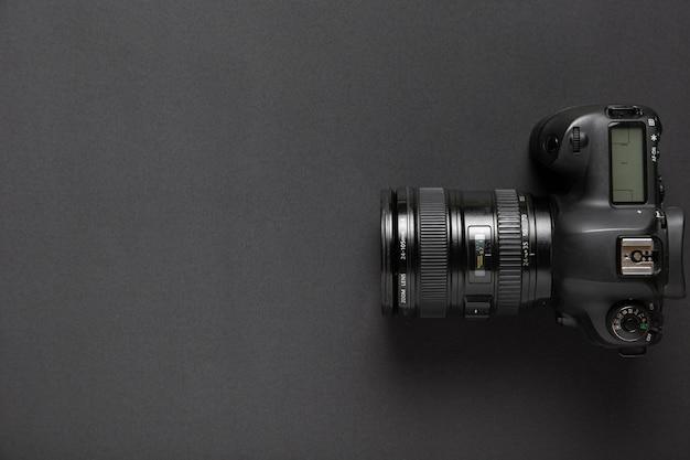 Disposizione piana della macchina fotografica su fondo nero con lo spazio della copia