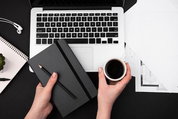 Disposizione piana della mano che tiene caffè e agenda