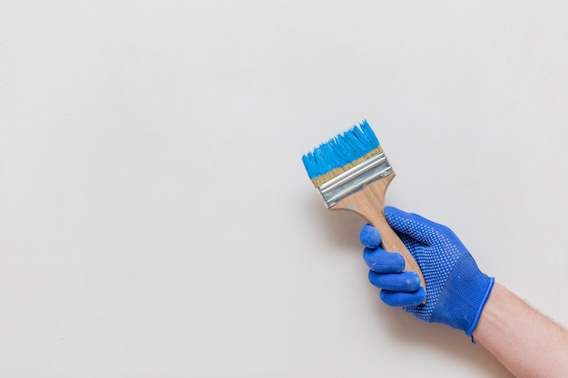 Disposizione piana della mano che tiene il pennello blu