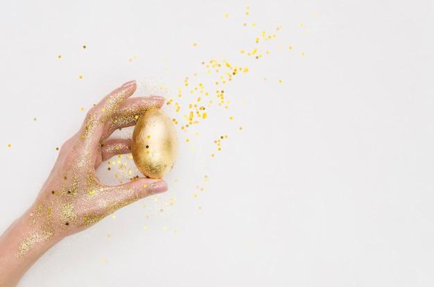Disposizione piana della mano che tiene l'uovo di pasqua dorato con lo spazio della copia e di scintillio