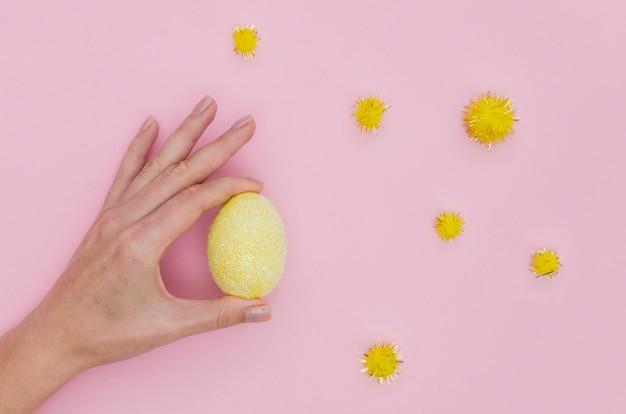 Disposizione piana della mano che tiene l'uovo di pasqua variopinto con i denti di leone