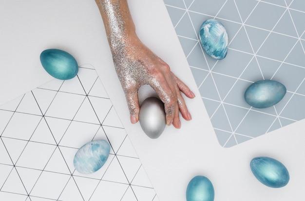 Disposizione piana della mano che tiene uovo tinto per pasqua