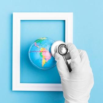 Disposizione piana della mano con lo stetoscopio della tenuta del guanto chirurgico sopra il globo della terra nel telaio