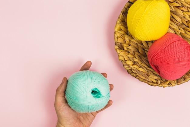 Disposizione piana della mano della donna che tiene la bella palla verde menta di lana di cotone accanto al rosa corallo e le palle gialle scure di lana di cotone in un cestino con sfondo rosa pastello e copia spazio