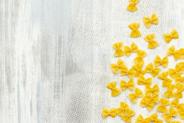 Disposizione piana della pasta del farfalle su fondo di legno con lo spazio della copia