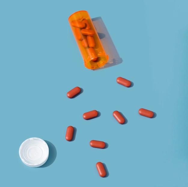 Disposizione piana della pillola rossa con contenitore di plastica