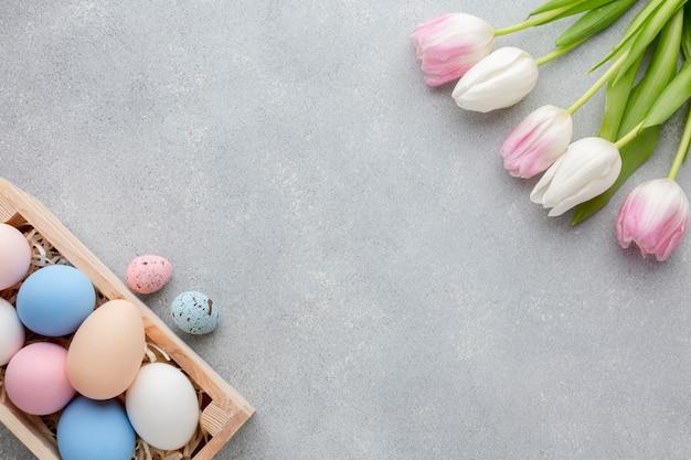 Disposizione piana della scatola con le uova di pasqua variopinte e i tulipani