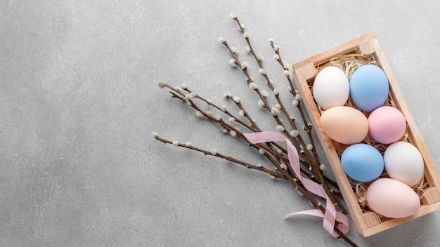 Disposizione piana della scatola con le uova di pasqua variopinte e lo spazio della copia