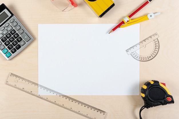 Disposizione piana della scrivania dell'architetto con foglio di carta