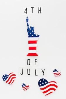 Disposizione piana della statua della libertà con le bandiere americane a forma di cuore per la festa dell'indipendenza