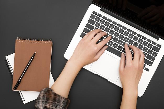 Disposizione piana della stazione di lavoro con le mani su laptop e notebook