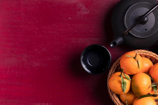 Disposizione piana della teiera e dei mandarini per il nuovo anno cinese