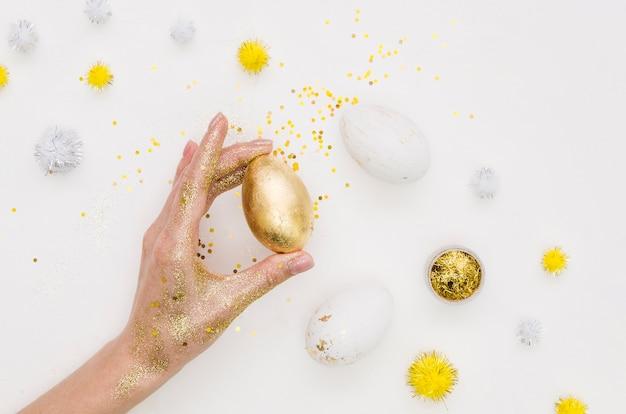 Disposizione piana della tenuta della mano che tiene uovo per pasqua con i denti di leone e lo scintillio