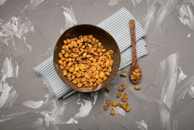 Disposizione piana delle arachidi in ciotola e cucchiaio