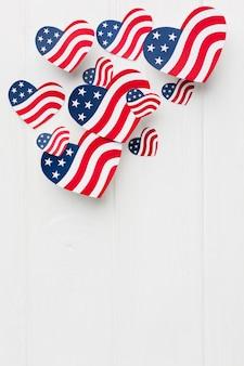 Disposizione piana delle bandiere americane a forma di cuore con lo spazio della copia