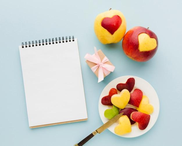 Disposizione piana delle figure del cuore della frutta con il taccuino e presente