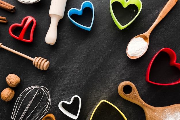 Disposizione piana delle forme colorate del cuore con delle forme colorate del cuore con gli utensili della cucina