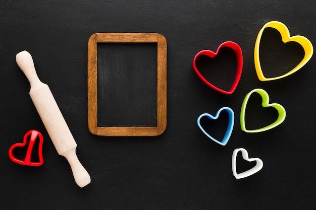 Disposizione piana delle forme colorate del cuore con il mattarello