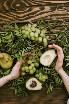 Disposizione piana delle mani della donna che tengono uva, pere e avocado con i rami del pistacchio
