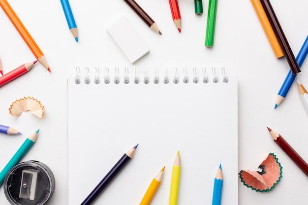 Disposizione piana delle matite variopinte e del taccuino