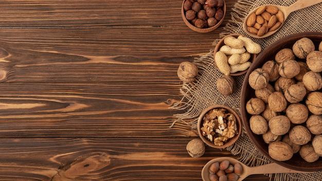 Disposizione piana delle noci in ciotola con altra varietà di noci e spazio della copia