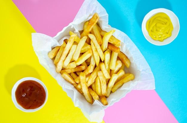 Disposizione piana delle patate fritte su fondo variopinto