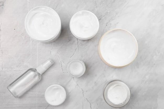 Disposizione piana delle scatole crema su fondo di marmo