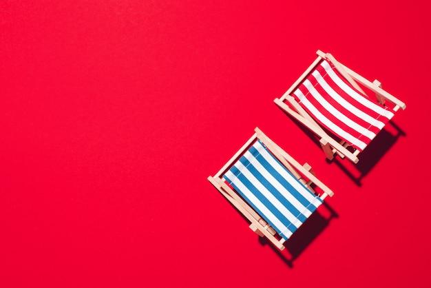 Disposizione piana delle sedie a sdraio della spiaggia su fondo rosso con lo spazio della copia.