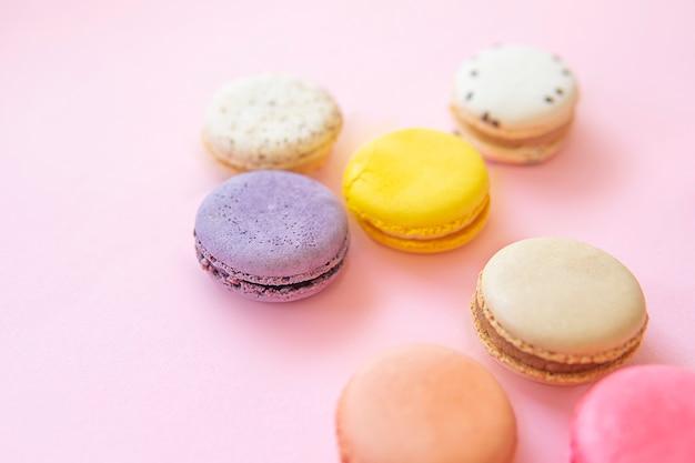 Disposizione piana delle torte di maccheroni variopinti francesi isolata su fondo rosa