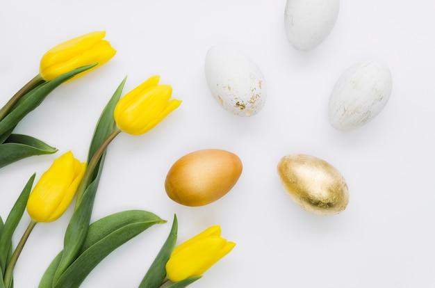 Disposizione piana delle uova di pasqua dorate con i fiori