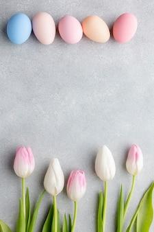 Disposizione piana delle uova di pasqua variopinte e dei tulipani sbalorditivi