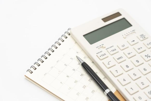 Disposizione piana dello scrittorio della tavola dell'ufficio di vista superiore con il calendario, le penne dei calcolatori e l'altro ufficio
