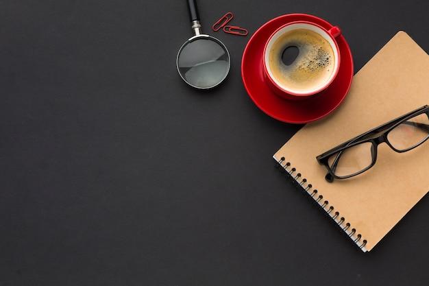 Disposizione piana dello spazio di lavoro con tazza di caffè e taccuino