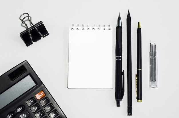Disposizione piana di affari, ufficio, contabilità, cancelleria della scuola sul tavolo, penna, matita, calcolatrice, taccuino con lo spazio della copia