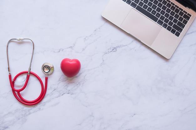 Disposizione piana di buon concetto sano, cuore rosso e stetoscopio e computer portatile su fondo di marmo bianco