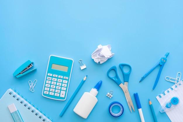 Disposizione piana di cancelleria per ufficio con calcolatrice e liquido di correzione