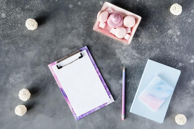 Disposizione piana di cancelleria per ufficio con una tazza di tè con marshmallow e laptop