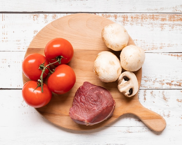 Disposizione piana di carne e verdure sulla tavola di legno