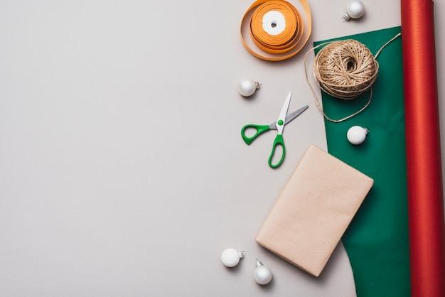 Disposizione piana di carta da imballaggio con spago e forbici