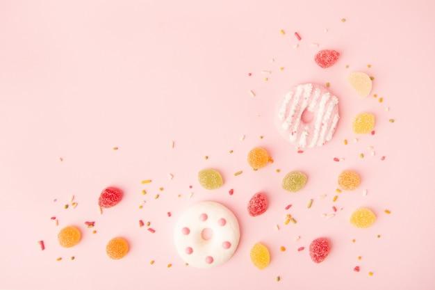 Disposizione piana di ciambelle glassate con caramelle e copia spazio